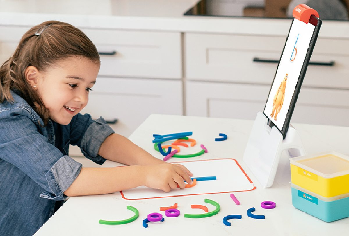 girl playing with STEM electronic learning kit at table in home