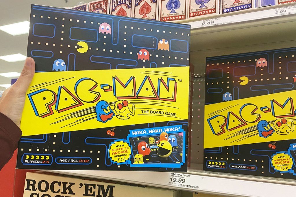 person holding up a black and yellow pac-man board game in front of target shelf