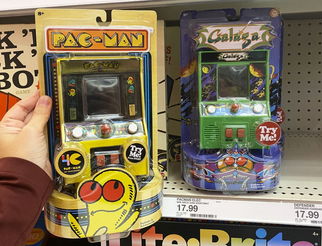 person holding up a yellow pac-man mini arcade machine game