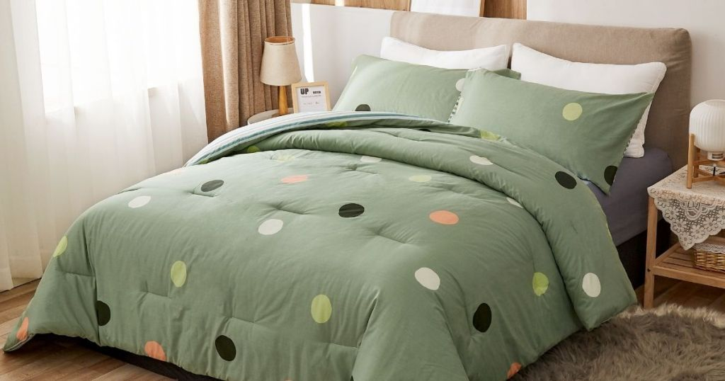 green and polka dot Peach Leaf comforter on bed