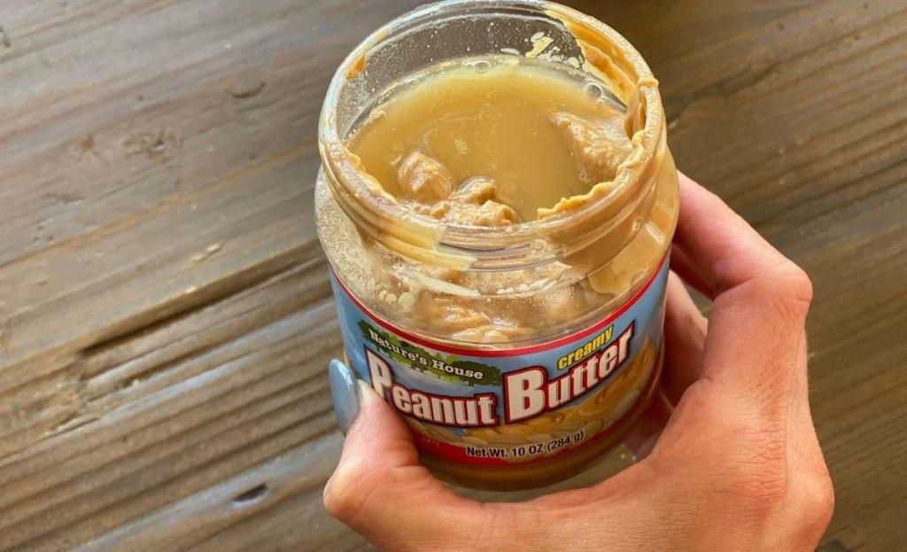 Sebuah tangan memegang toples selai kacang