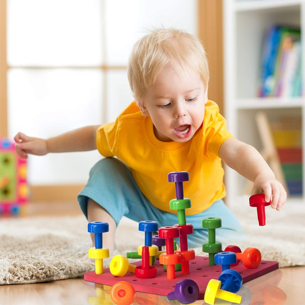 toddler playing with Pegboard Set