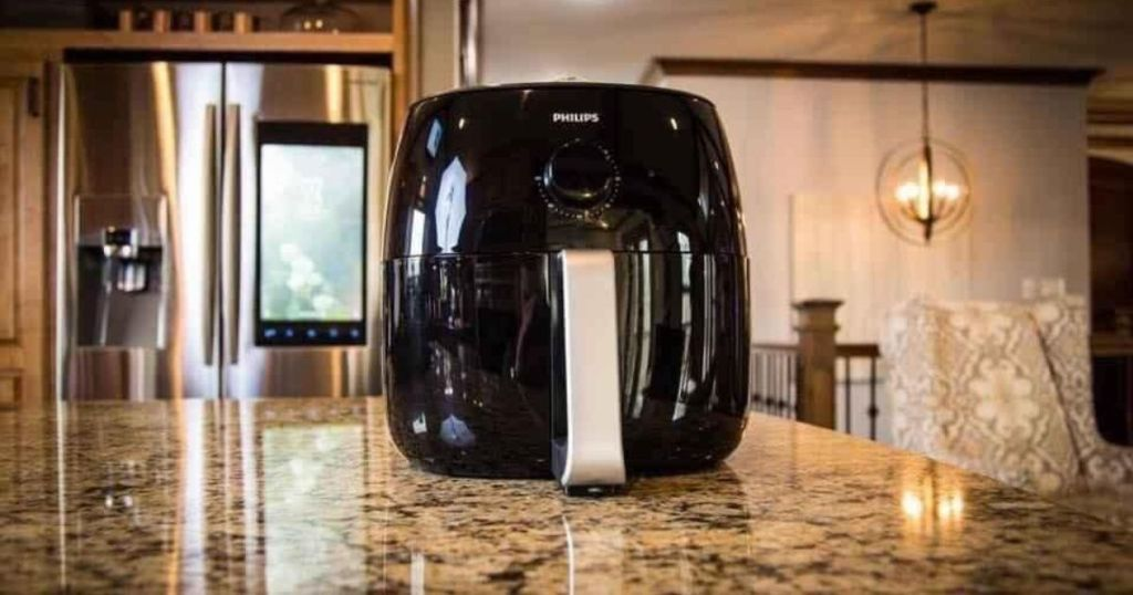 black analog air fryer on marble counter in kitchen