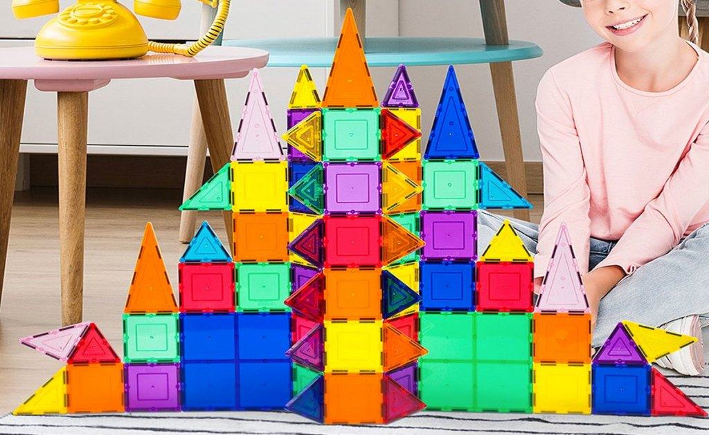 girl playing with rainbow magnetic tile set in shape of a castle