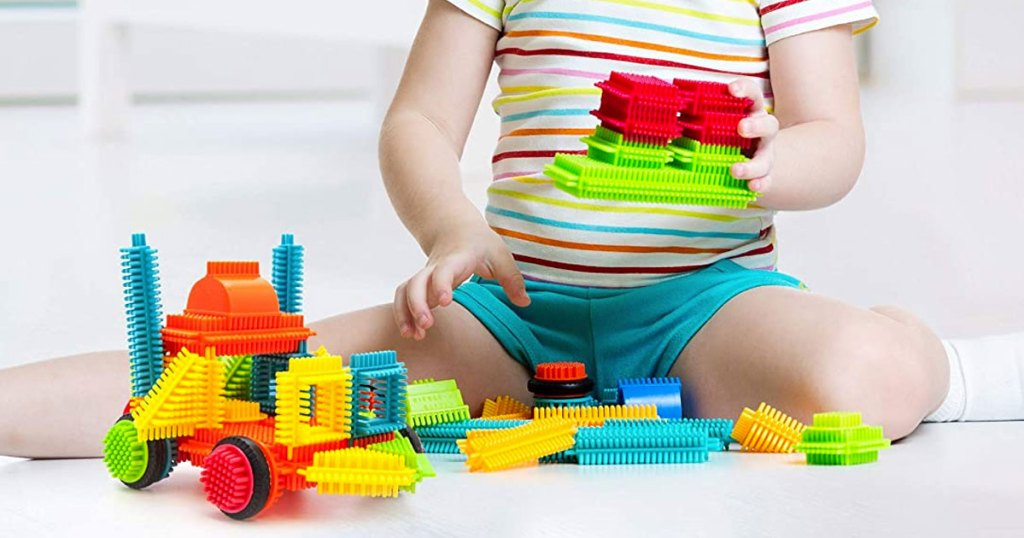 girl in striped shirt sitting on floor playing with multi-color bristle blocks