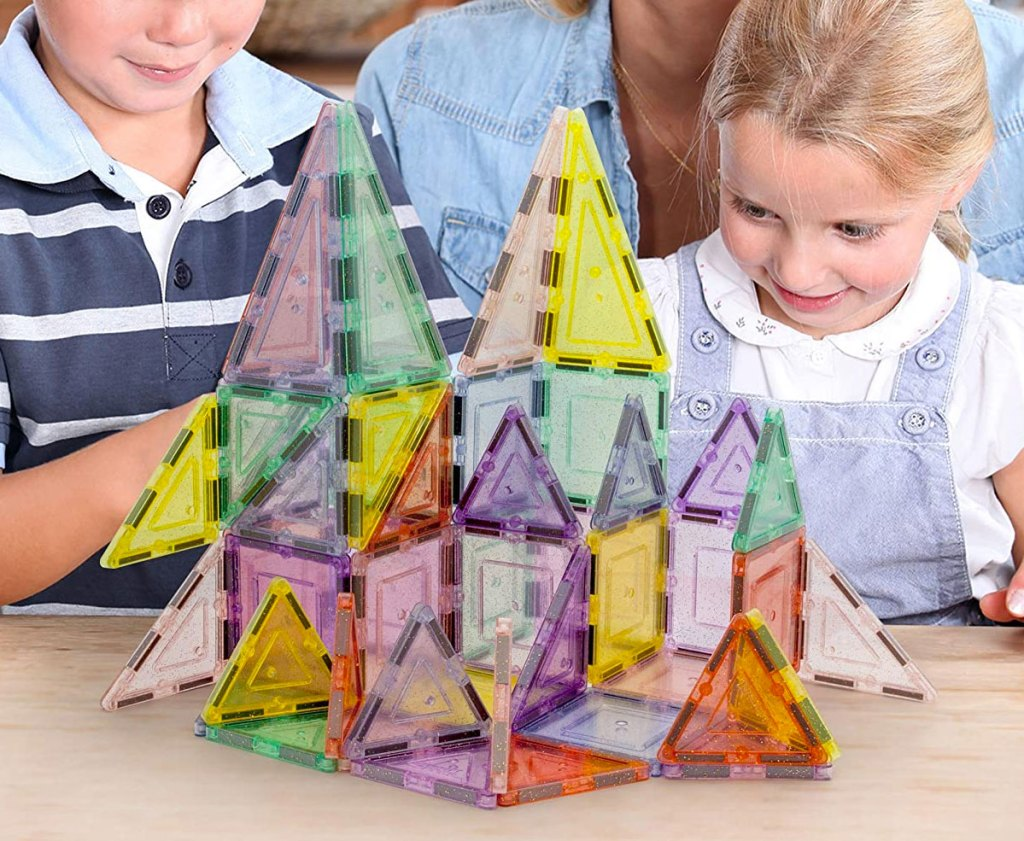 girl and boy playing with a glittery magnetic building block set