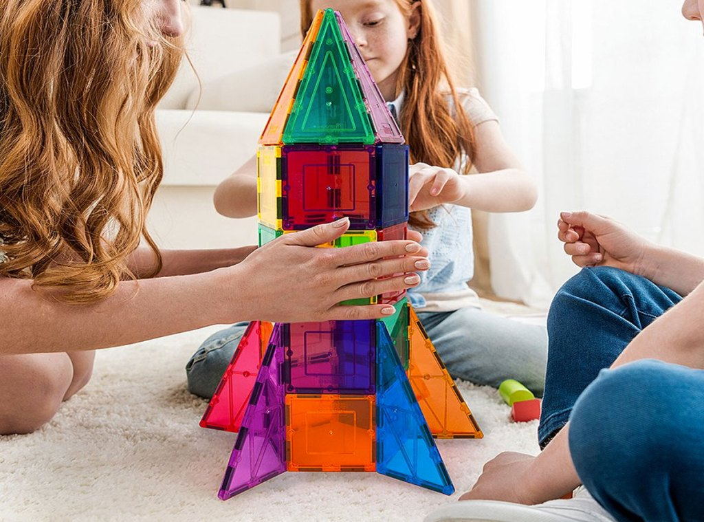 kids playing with magnetic building block set in the shape of a rocket