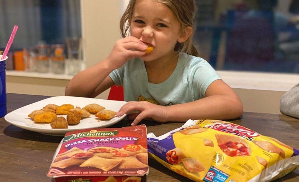 Seorang gadis kecil sedang makan pizza roll di meja