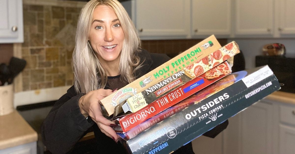 A woman holding boxes of frozen pizza in a kitchen for the best pepperoni pizza taste test
