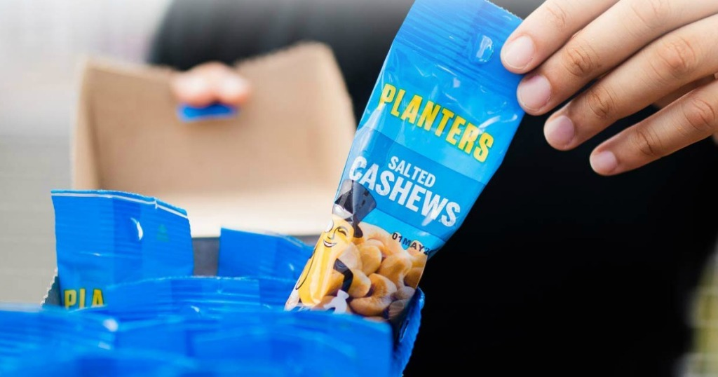 Hand pulling out a small package of cashews
