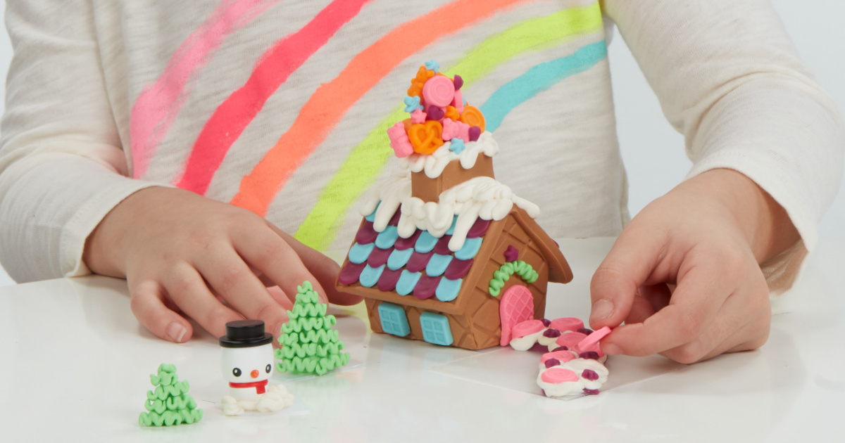 little girl playing with a Play-Doh Gingerbread House kit
