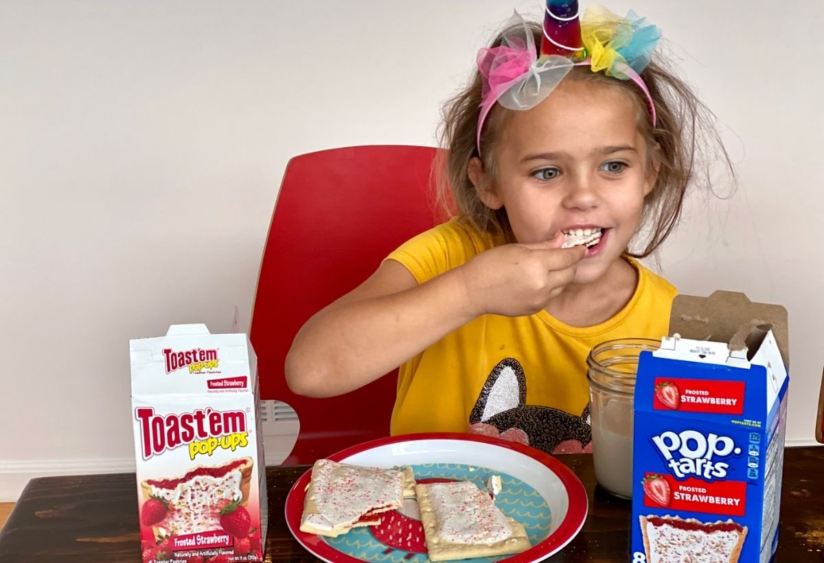 A little girl eating pop tarts at a table