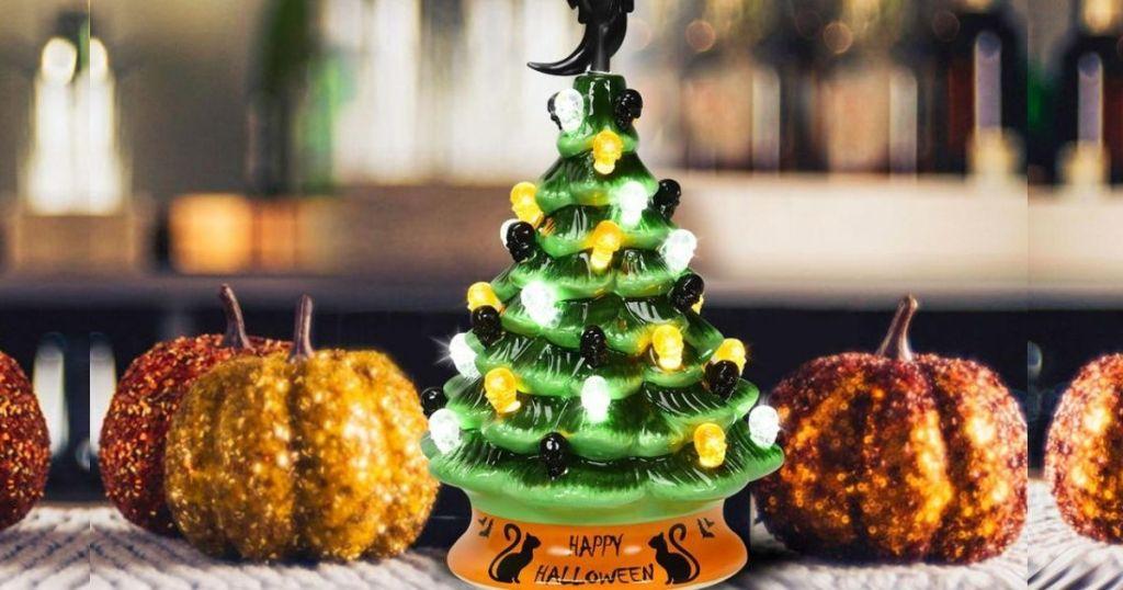 ceramic Halloween Tree with glittery pumpkin decorations beside it
