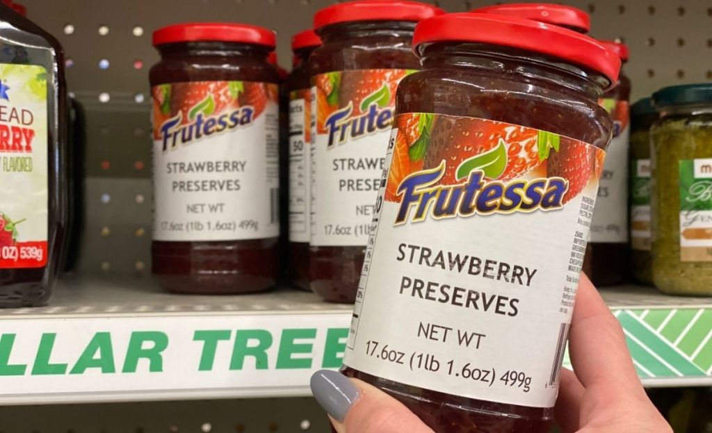 A hand holding a jar of strawberry preserves at a store