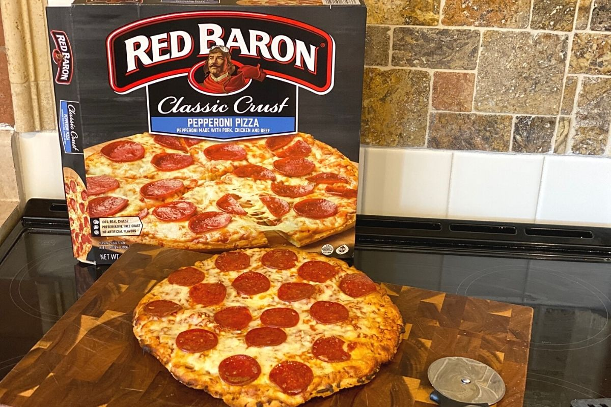 red baron pizza next to the box on a stove