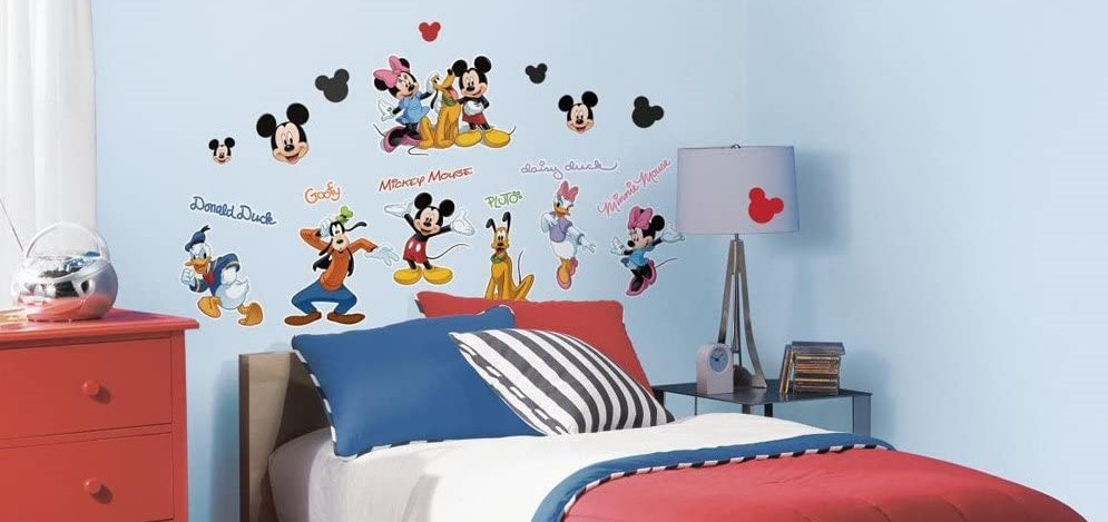 bedroom with bed and Disney character decals on the wall