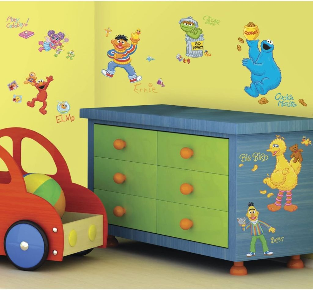 room with Sesame Street decals on wall and dresser