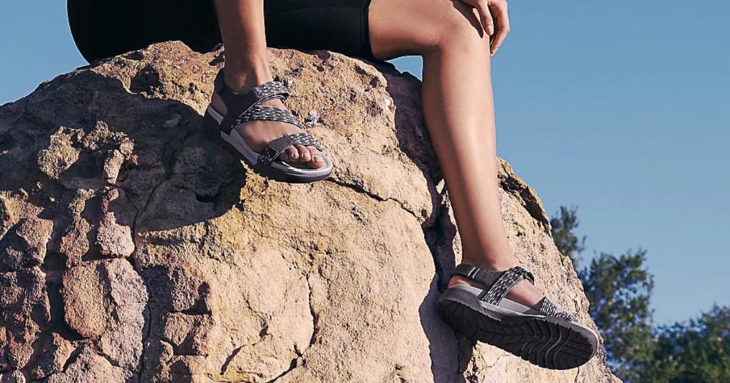 women wearing Ryka Sport Sandals on a large rock