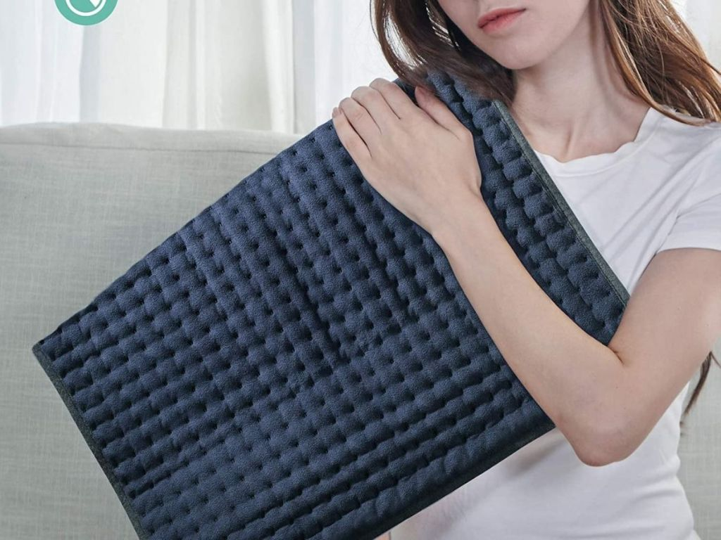 woman with large heating pad on her shoulder