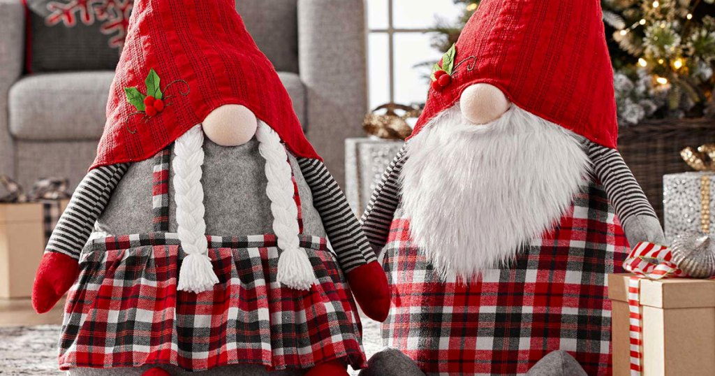 set of two oversize christmas themed gnomes on floor near christmas tree