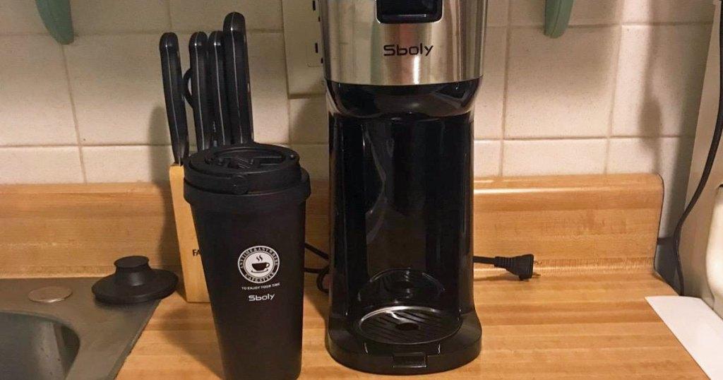 black single seve coffee maker with black travel mug on kitchen counter