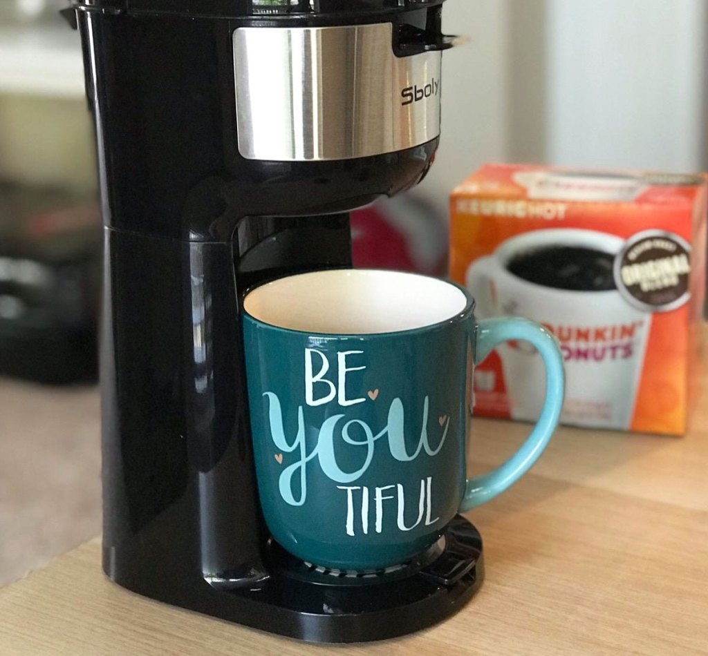 black single serve coffee maker with blue mug that says be-you-tiful