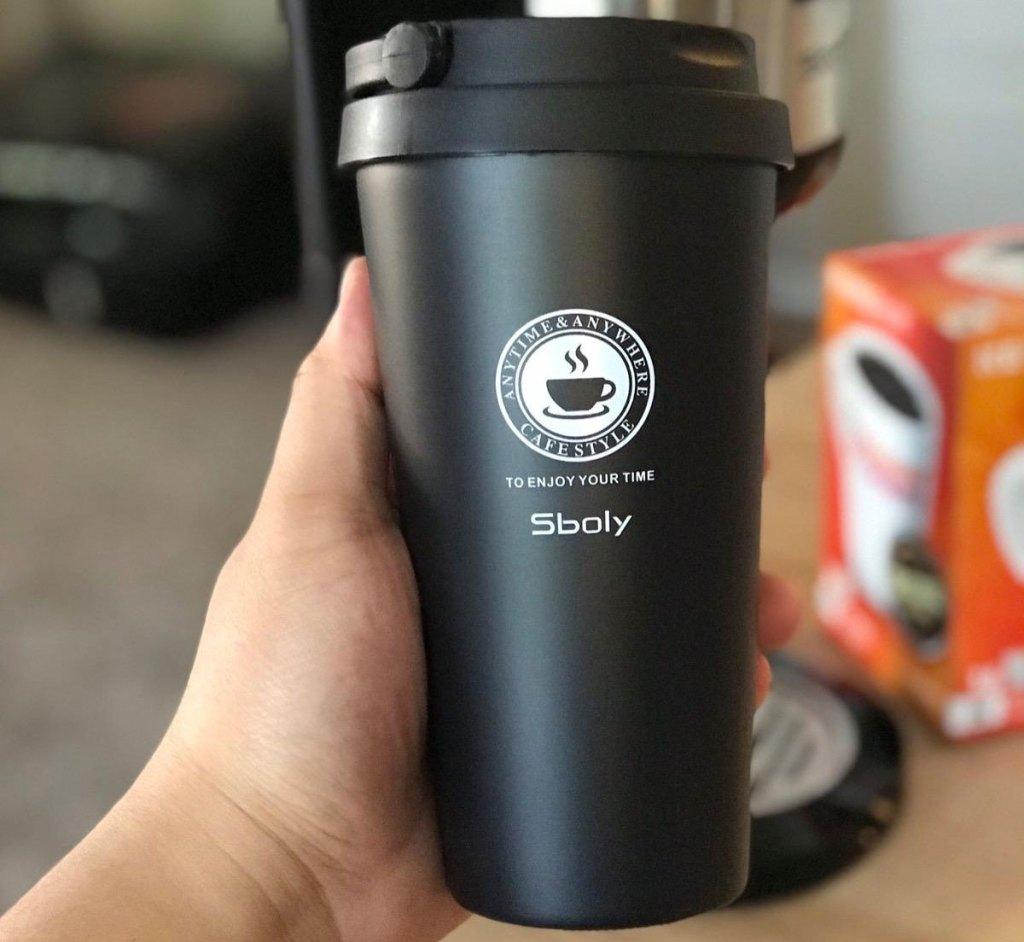 person holding up black travel coffee mug