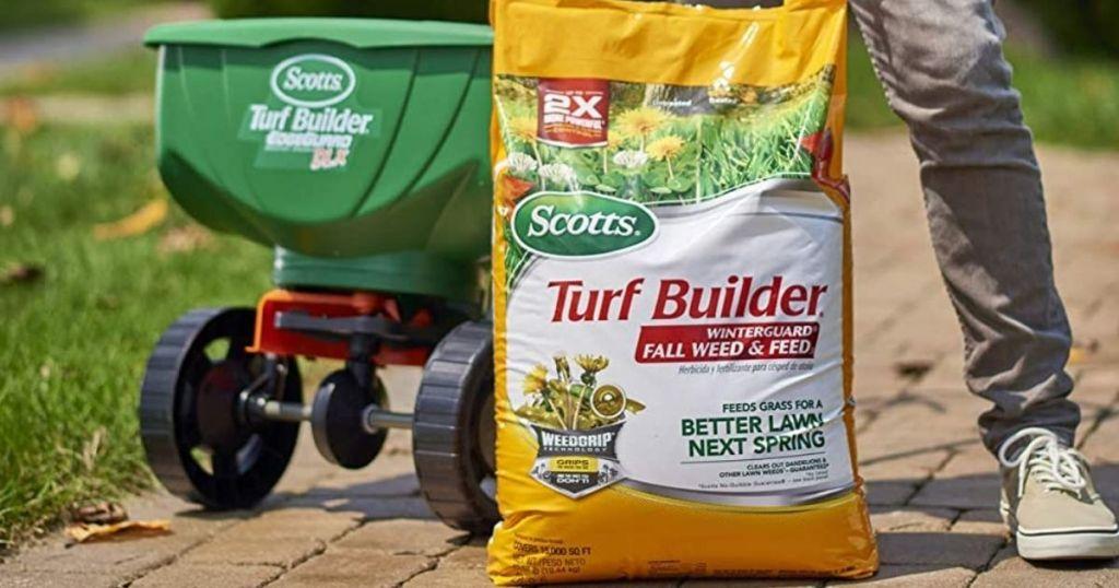 bag of lawn fertilizer by spreader cart