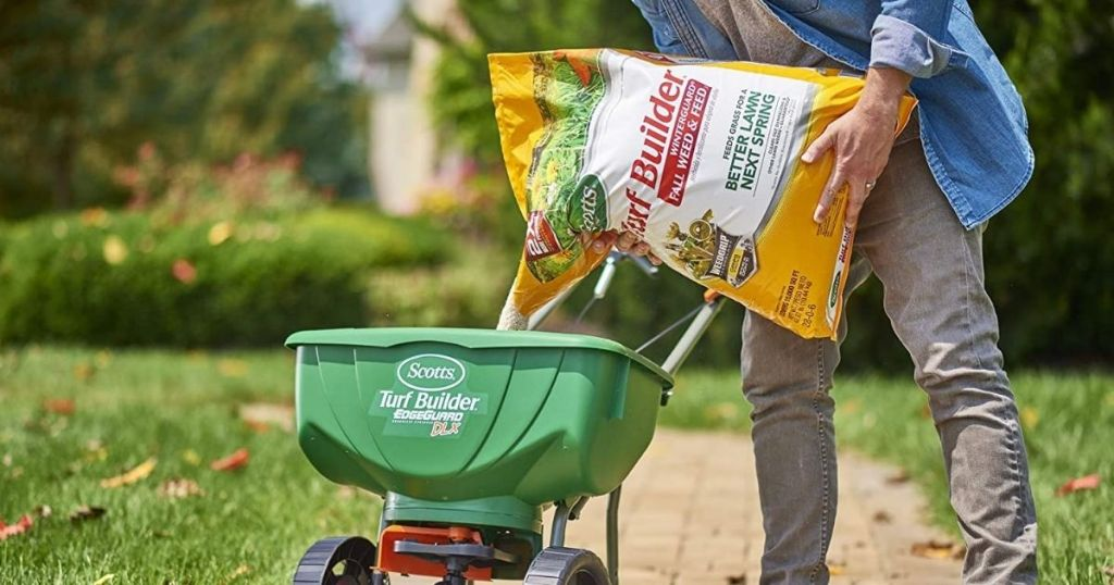 man pouring lawn fertilizer into spreader cart