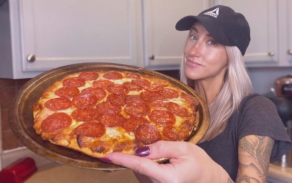 A woman holding a screamin sicilian pizza