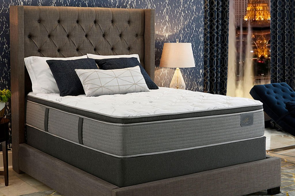 pillow-top mattress on a boxspring with a grey upholstered headboard