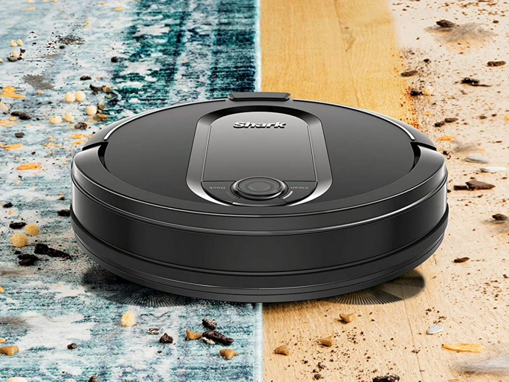 Black robot vacuum cleaning up dirt on carpet and hardwood flooring