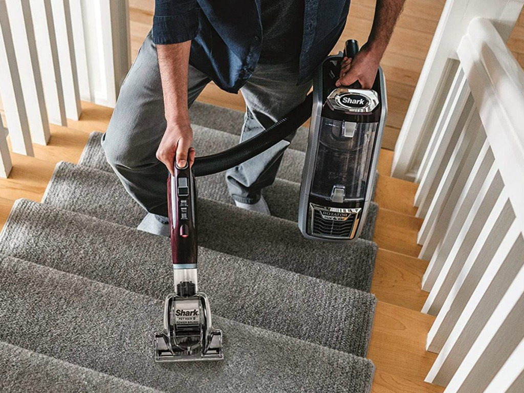 Man using a lift-away vacuum on carpetted stairs