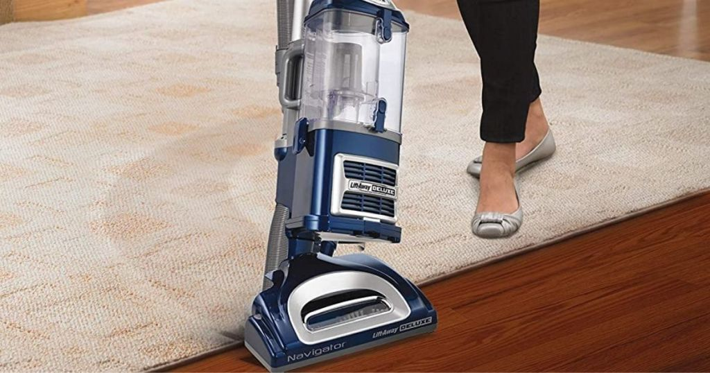 Shark navigator with lady vacuuming carpet to hardwood