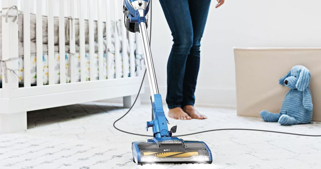 woman cleaning rug in nursery with a blue shark stick vacuum