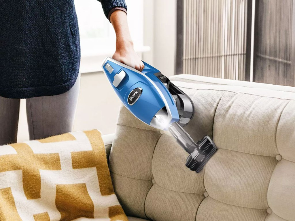 person using a blue handheld shark vacuum to clean a couch