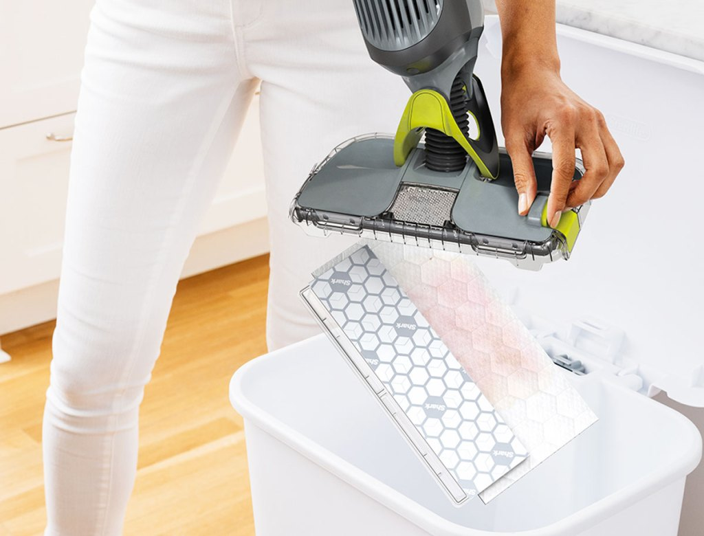 woman in white jeans pressing release button to remove the wet pad from shark vacmop into trash can