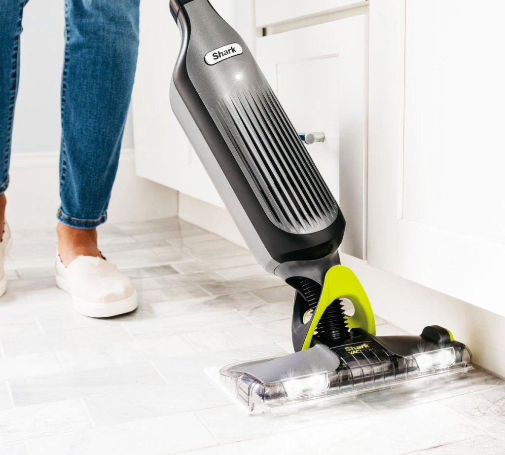 person using a black and grey shark vacmop on white tile floors