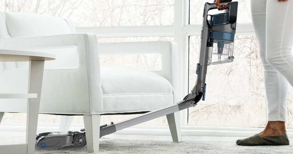 person using a shark stick vacuum to clean under a white chair