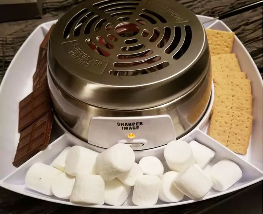 stainless steel smores grill with chocolate, marshmallows, and graham crackers in tray around it