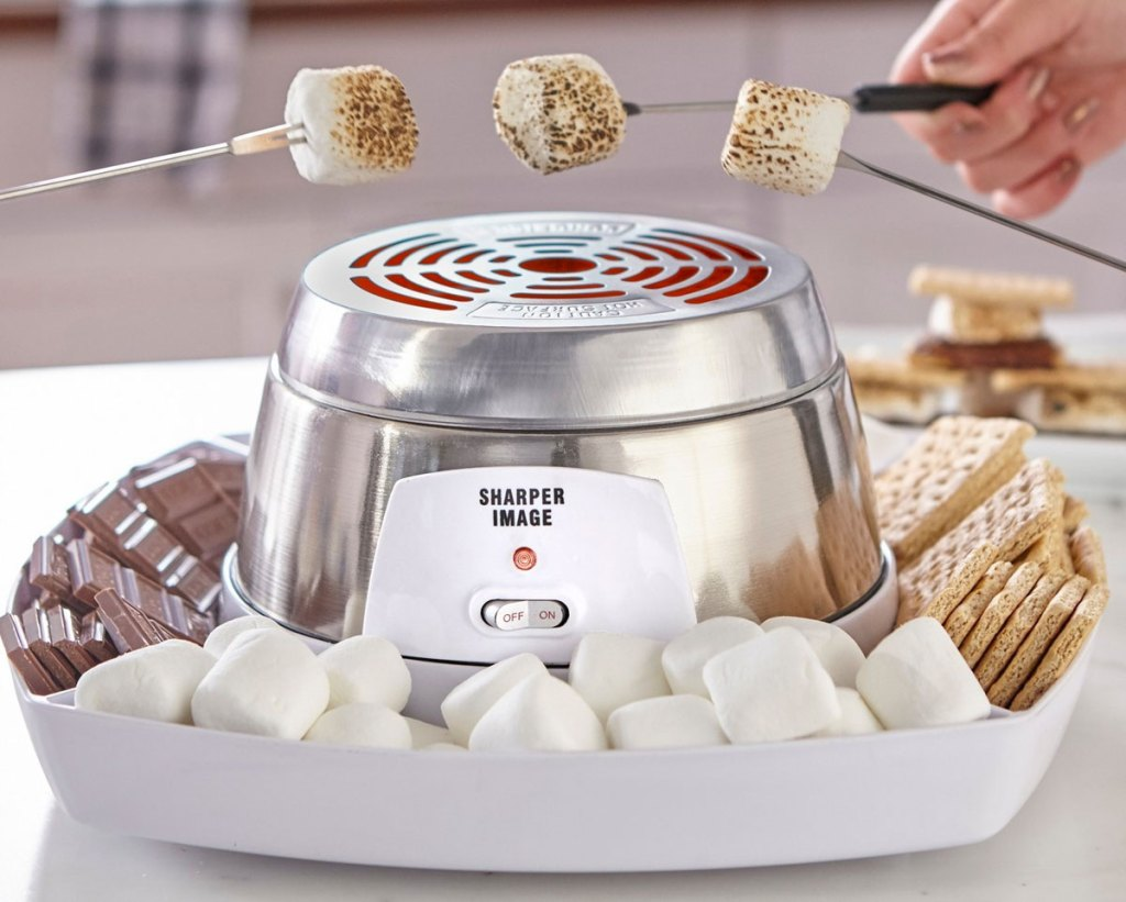 three people roasting marshmallows over a stainless steel smores maker with ingredients in tray around it