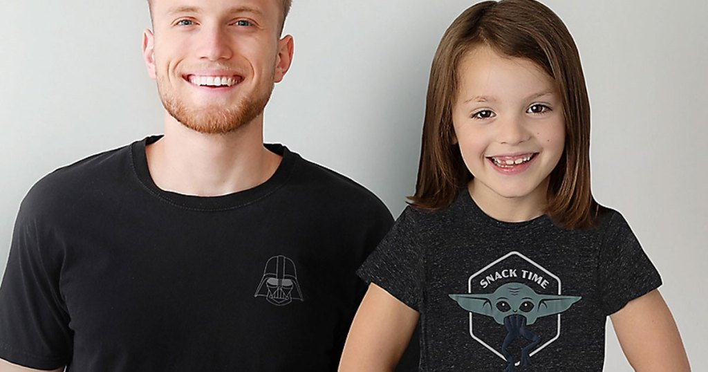 man in black darth vader tee and girl in mandalorian child with frog tee