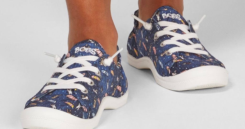 woman wearing a pair of blue sneakers with raining cats and dogs print