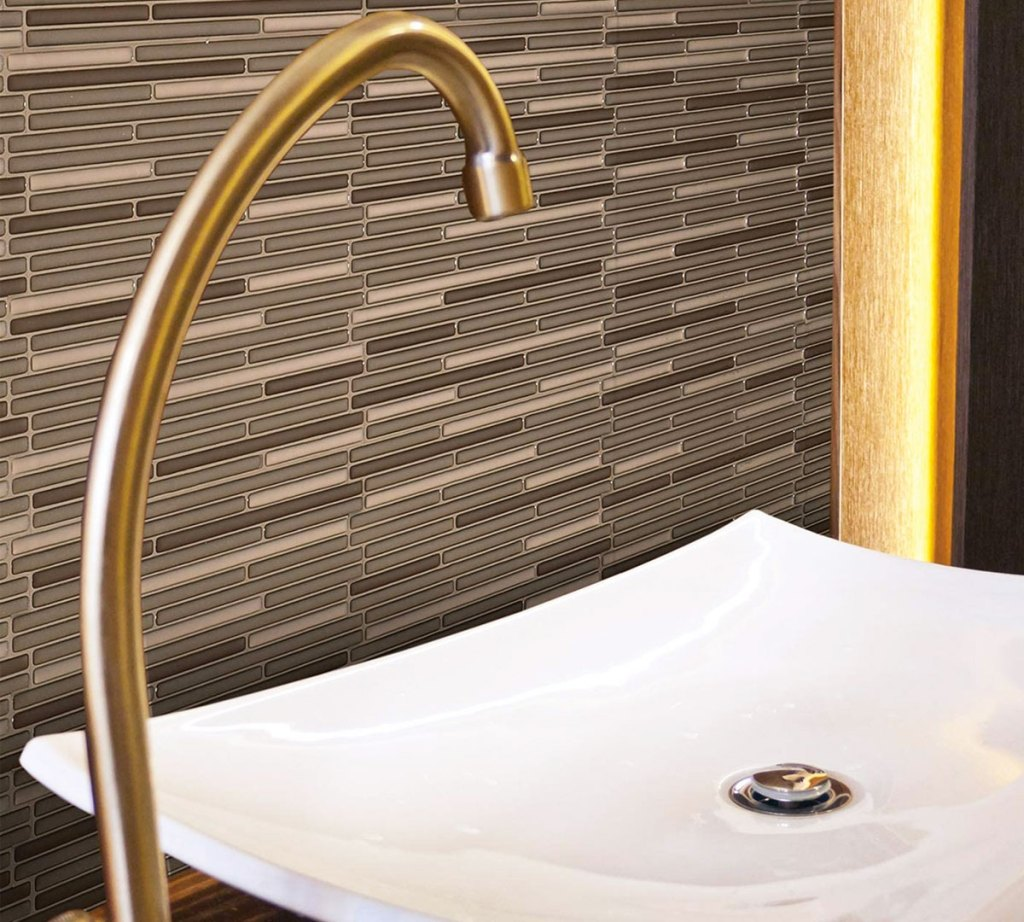 neutral and brown peel and stick wall tiles behind bathroom sink