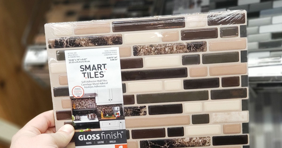 person holding up a set of smart tiles peel and stick wall tiles