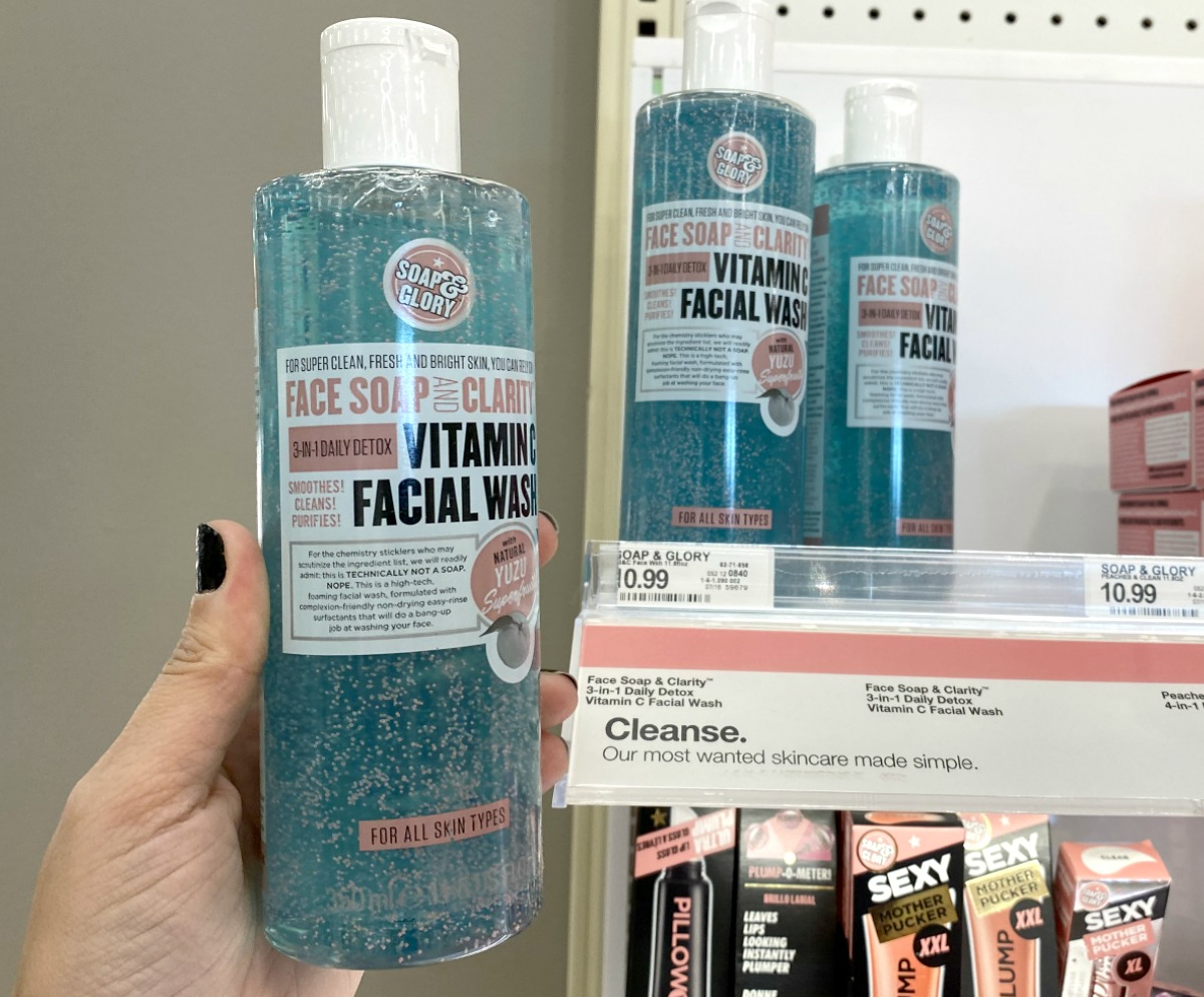 Hand holding a bottle of blue face wash near in-store display