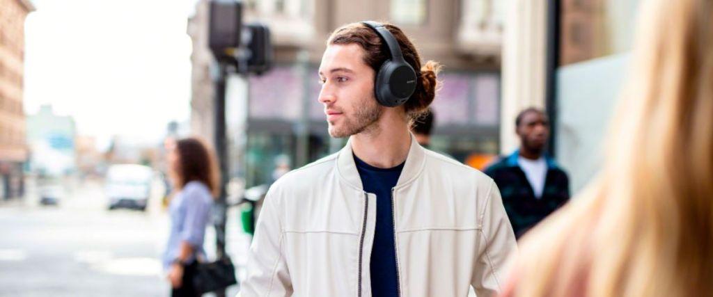 man walking on the street with headphones on