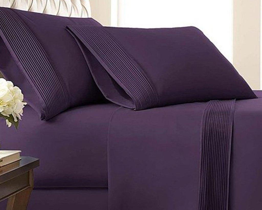 dark purple sheet on bed with matching pillow cases and pleated design on edges