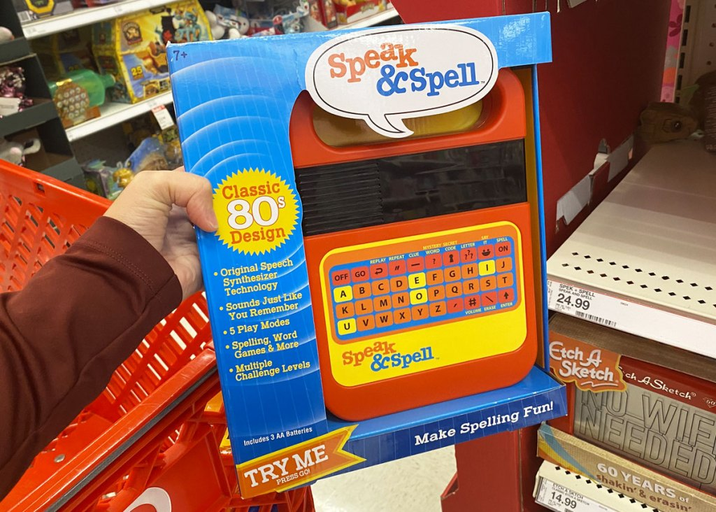 person holding up electronic speak & spell game in front of red target shopping cart