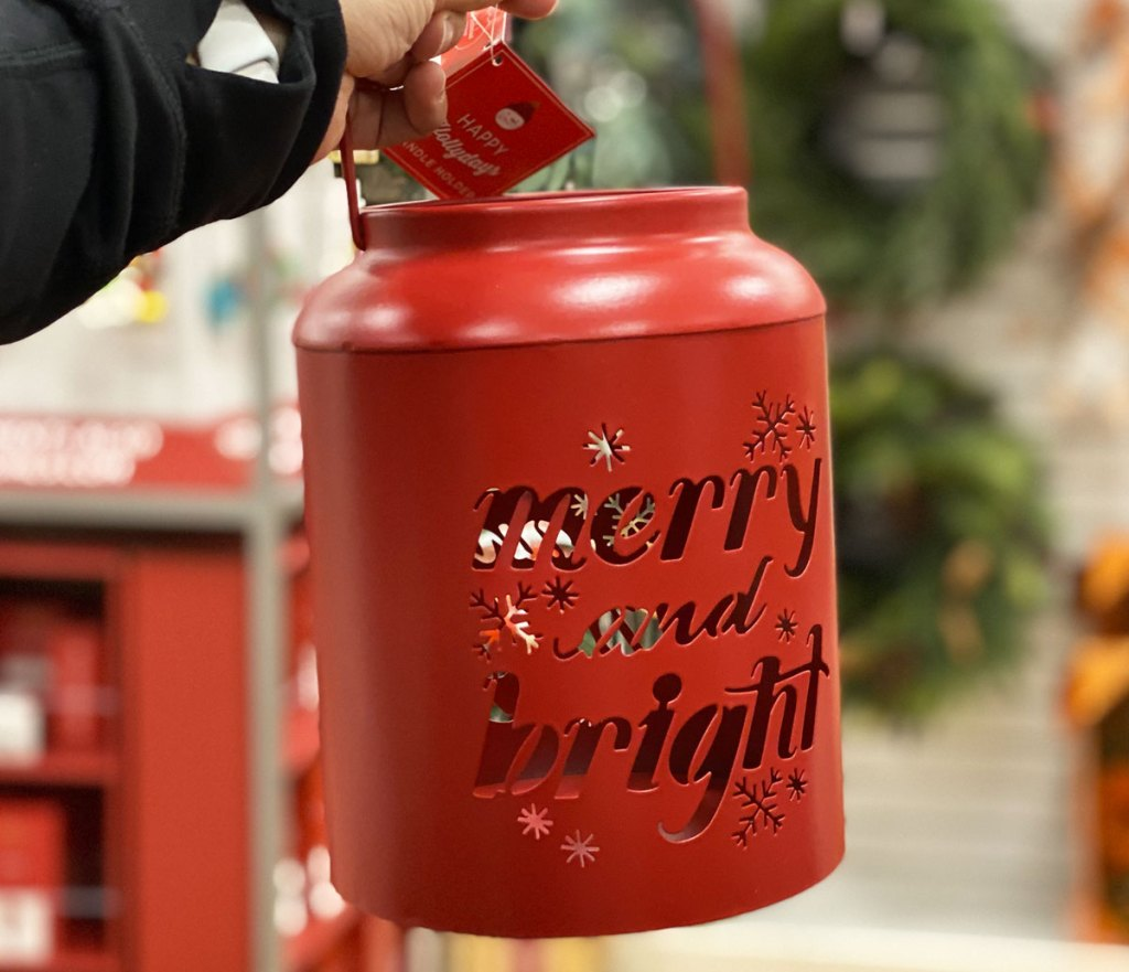 woman holding up red metal lantern that says merry and bright in cut out letters
